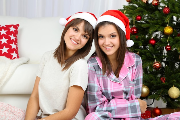 Hermosas chicas gemelas en pijama cerca del árbol de navidad en casa
