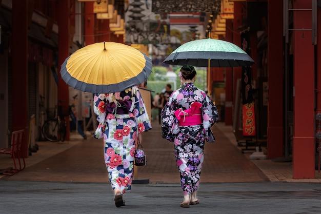 Hermosas chicas japonesas en kimono y con paraguas.