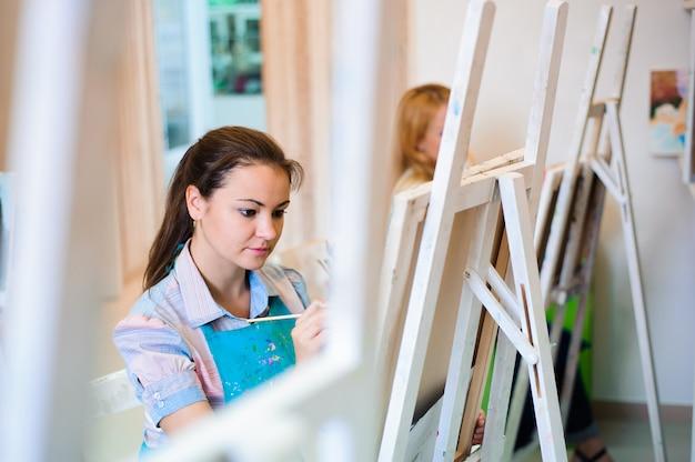 Hermosas chicas jóvenes dibujan pinturas en una lección de arte