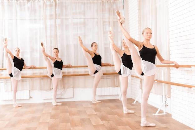 Hermosas chicas jóvenes entrenan en el salón de ballet.