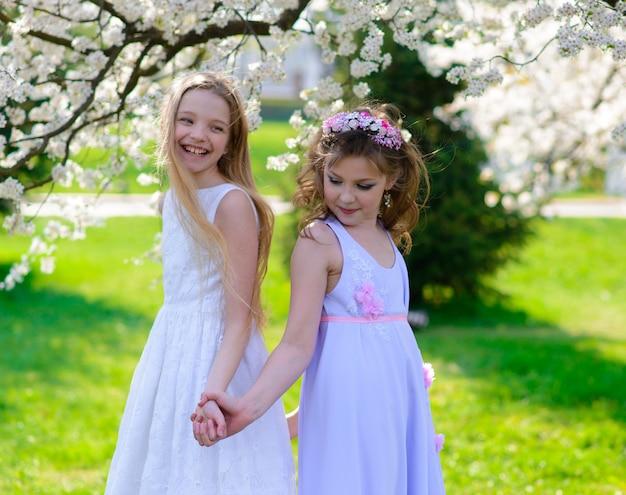 Hermosas chicas jóvenes con ojos azules en un jardín de vestidos blancos con manzanos floreciendo divirtiéndose y disfrutando el olor del jardín floreciente de primavera.