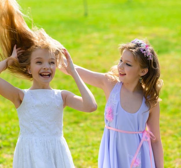 Hermosas chicas jóvenes con ojos azules en vestidos blancos en el jardín con manzanos floreciendo divirtiéndose y disfrutando del olor del jardín floreciente de primavera.