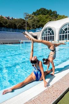 Hermosas chicas jóvenes posando junto a la piscina