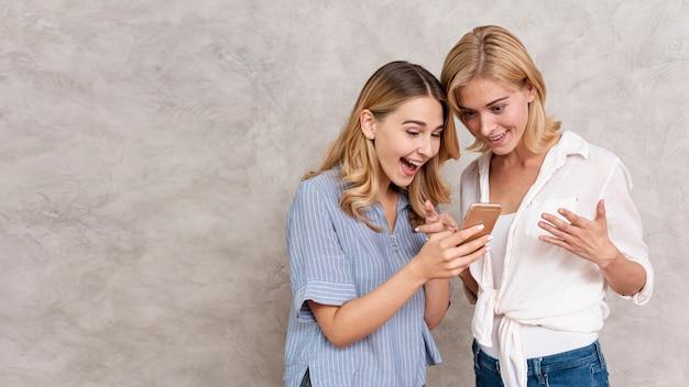 Hermosas chicas jóvenes revisando un mensaje
