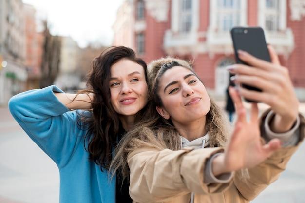 Hermosas chicas jóvenes tomando una selfie juntos