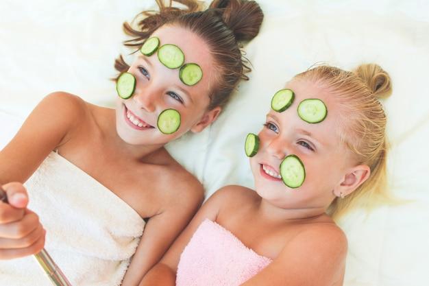 Hermosas chicas con mascarilla facial de pepino. los niños tomaron fotografías de ella misma.