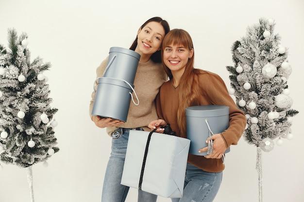 Hermosas chicas de pie en un estudio con regalos