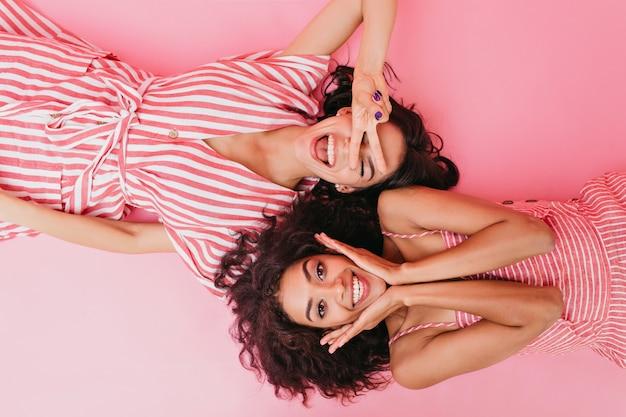 Hermosas chicas de piel oscura con lindas sonrisas se divierten y están acostadas de espaldas.