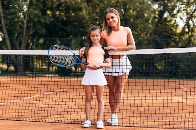 Hermosas chicas preparándose para hacer ejercicio en la cancha de tenis