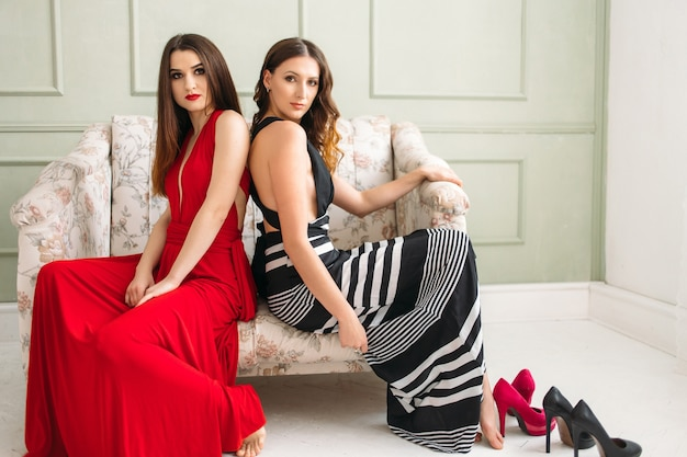 Las hermosas chicas sentadas en el sofá