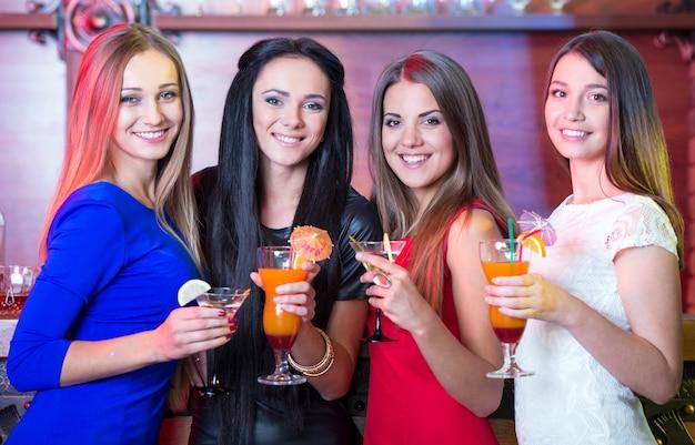 Hermosas chicas se sientan en el bar en sus manos con cócteles.