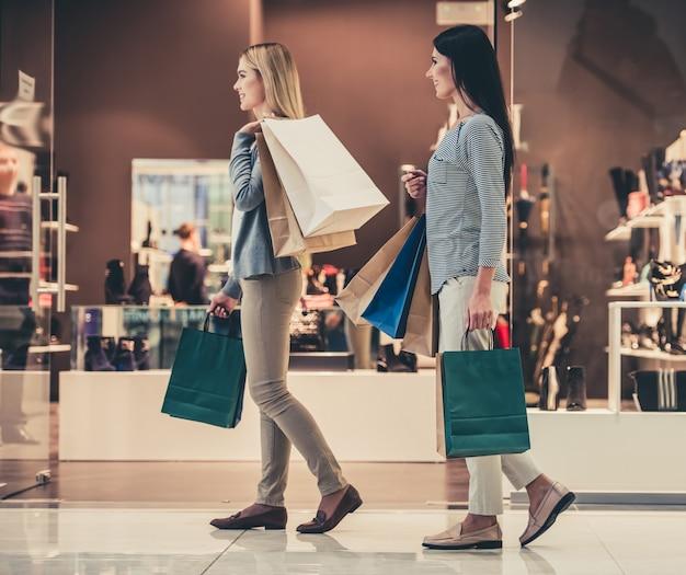 Hermosas chicas sonríen mientras hacen compras en el centro comercial