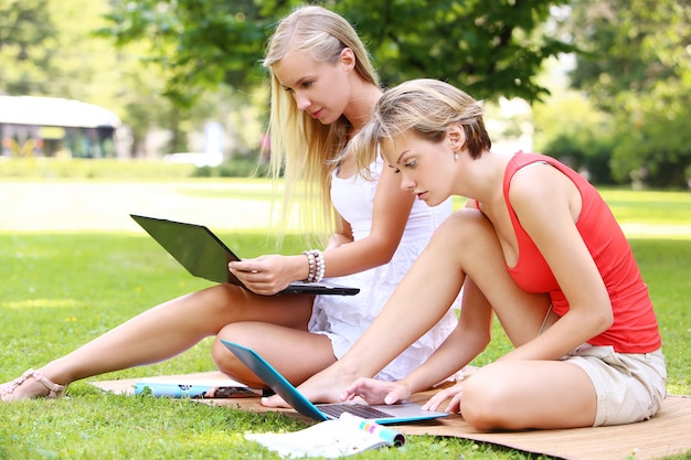 Hermosas chicas usando computadoras portátiles en un parque