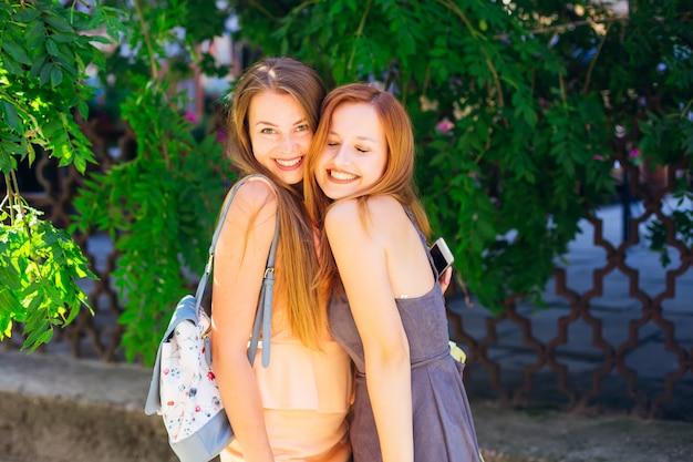 Hermosas chicas en vestidos abrazan y ríen de buena gana