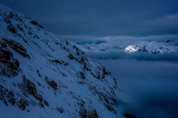 Hermosas colinas y montañas nevadas en la noche con un cielo nublado impresionante