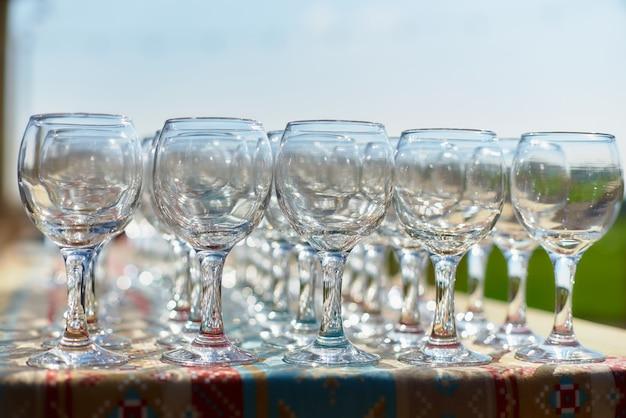 Hermosas copas de vino de mesa para vacaciones, dos filas de copas en una mesa con un mantel blanco, anteojos con patas altas colocan una copa de vino en la mesa festiva