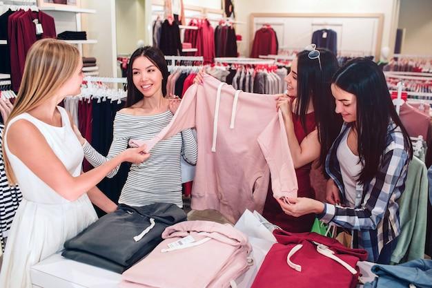 Hermosas damas están en la tienda. están sosteniendo una sudadera deportiva rosa.