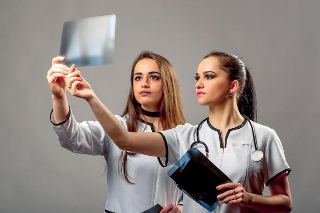 Hermosas doctoras con batas médicas con estetoscopios mirando rayos xy discutiendo los resultados.