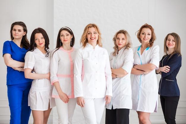Hermosas doctoras jóvenes en uniformes blancos posando sobre el fondo de una pared blanca.