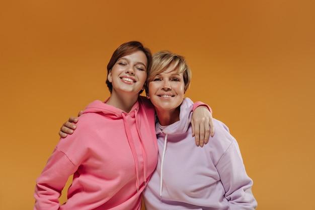 Hermosas dos damas con peinado corto y moderno en amplias sudaderas con capucha brillantes sonriendo y abrazándose sobre fondo naranja aislado.
