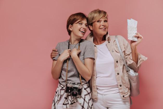 Hermosas dos mujeres con peinado corto con estilo en ropa moderna abrazándose, riendo y sosteniendo dos boletos y cámara sobre fondo rosa.