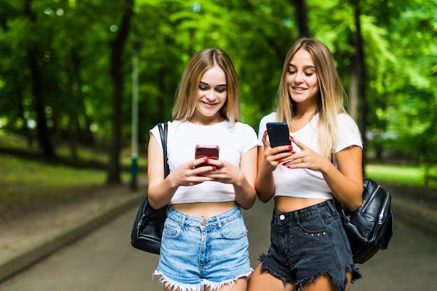 Hermosas dos mujeres que usan móviles en el parque. amigos y concepto de verano.