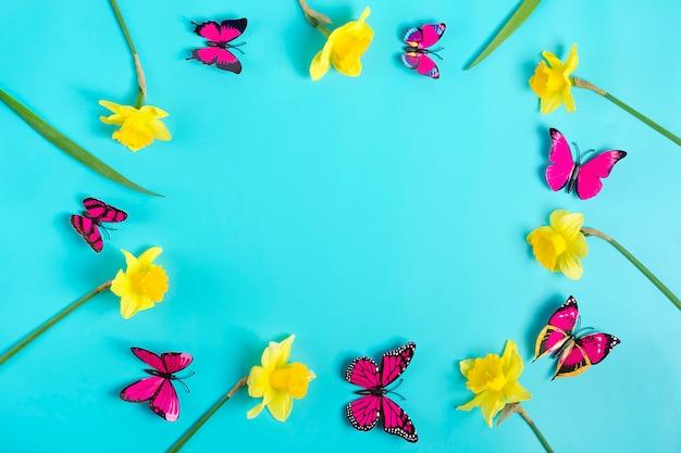 Hermosas flores amarillas de narcisos, mariposa sobre fondo azul