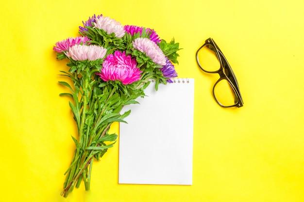 Hermosas flores de aster, bloc de notas blanco sobre fondo de color amarillo pastel