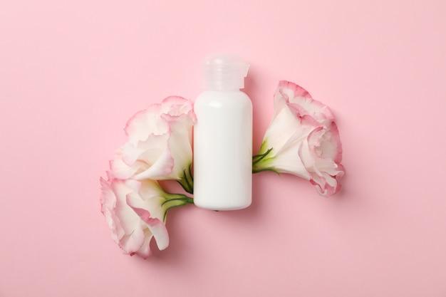 Hermosas flores y botella en blanco sobre fondo rosa, espacio para texto