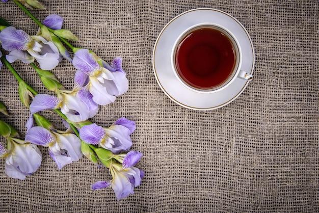 Hermosas flores de color púrpura iris y una taza de té sobre un fondo de lienzo gris
