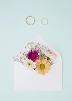 Hermosas flores dentro del sobre blanco con dos anillos de boda sobre fondo azul