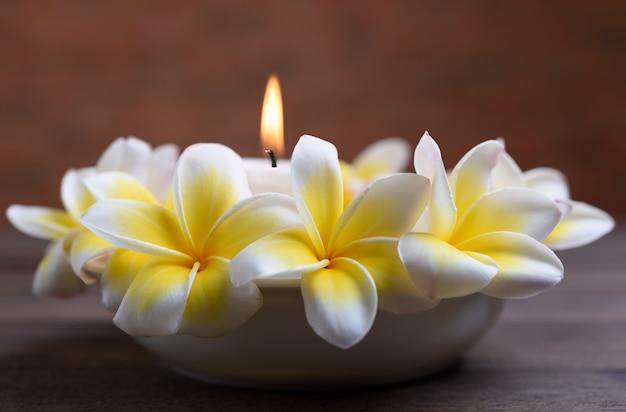 Hermosas flores frangipani en un tazón blanco y luz de velas en la mesa de madera, concepto de relajación y meditación