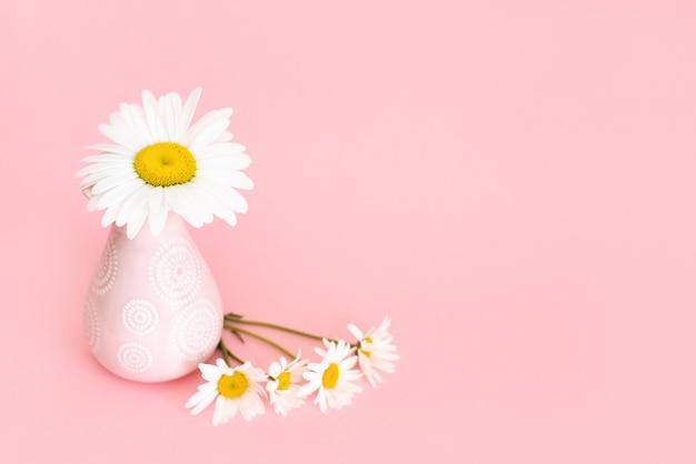 Hermosas flores en un jarrón sobre un fondo de pared rosa