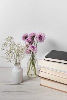 Hermosas flores junto a la pila de libros