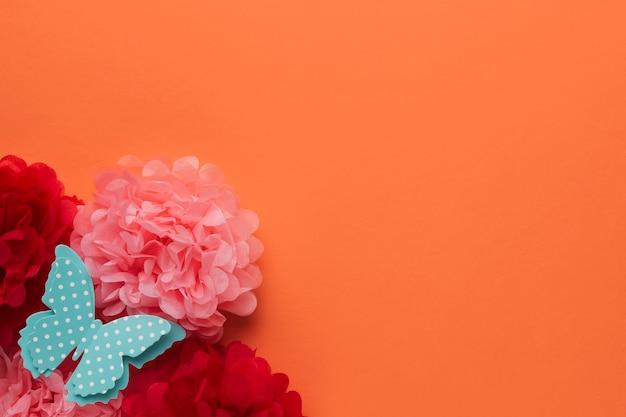 Hermosas flores de papel de origami y mariposa azul con lunares sobre fondo naranja