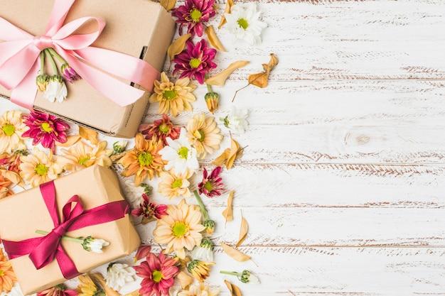 Hermosas flores y regalo envuelto con espacio de copia de texto