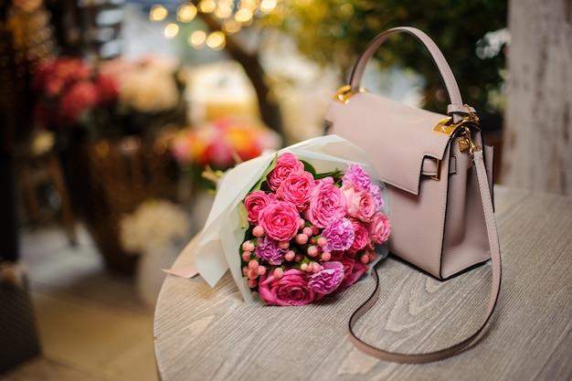 Hermosas flores rosadas cerca del elegante bolso sobre la mesa