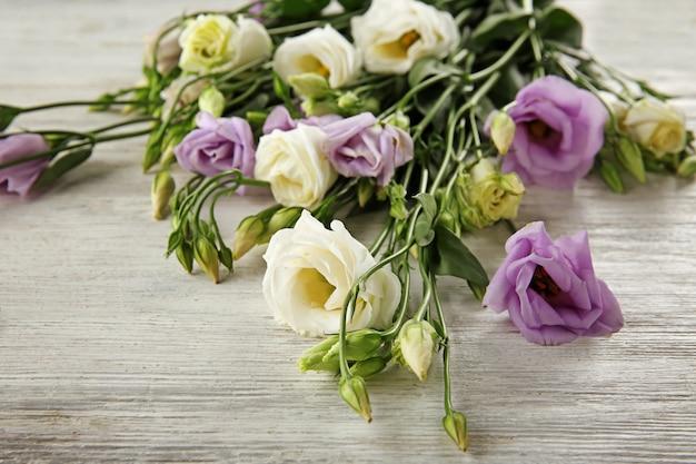Hermosas flores en superficie de madera