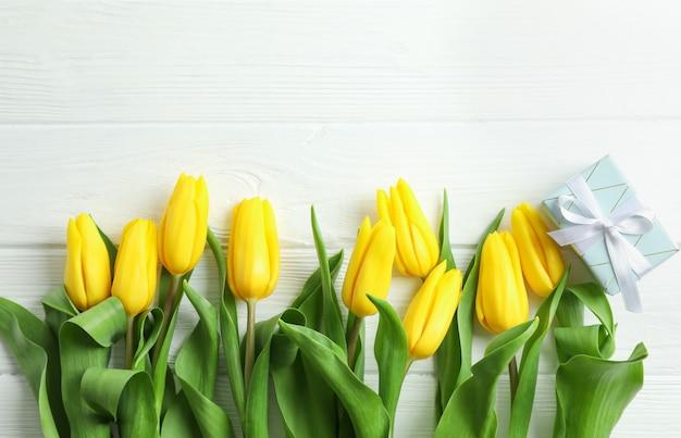 Hermosas flores de tulipán amarillo y caja de regalo en madera. espacio para texto