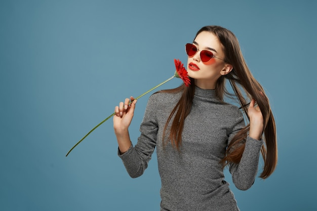 Hermosas gafas de sol morenas flor roja cerca de fondo azul de cosméticos de cara