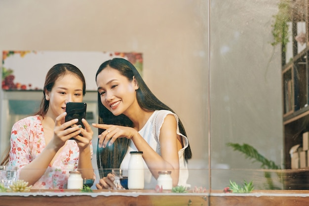 Hermosas jóvenes amigas vietnamitas revisando fotos que acaban de hacer en el teléfono inteligente