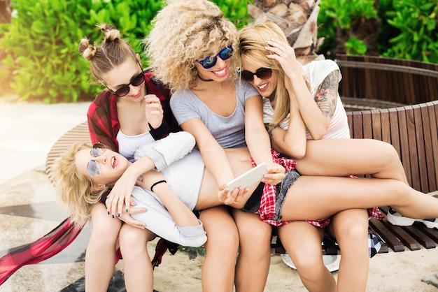 Hermosas jóvenes amigos relajarse fuera tomando selfie grupal sonriendo