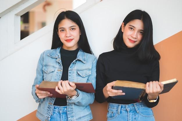 Hermosas jóvenes estudiantes abren libros para leer en la universidad.