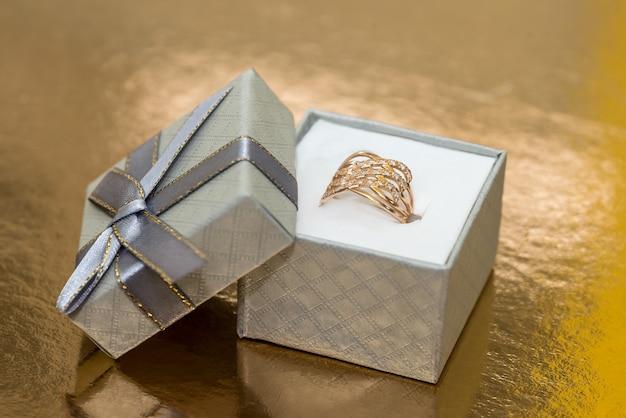 Hermosas joyas de oro en caja de regalo en pared dorada