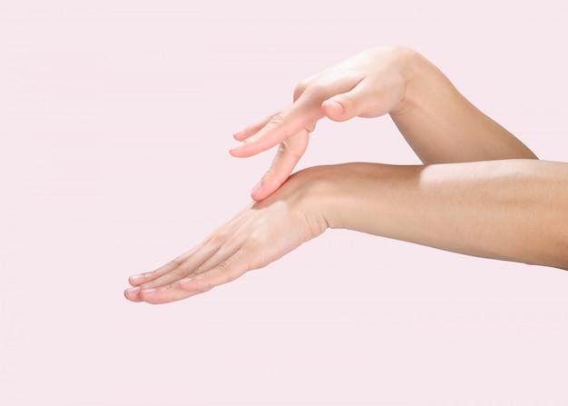 Hermosas manos aisladas, aplicando crema, masajeando con trazado de recorte.