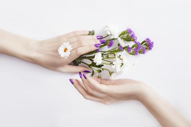 Hermosas manos bien cuidadas con flores silvestres.