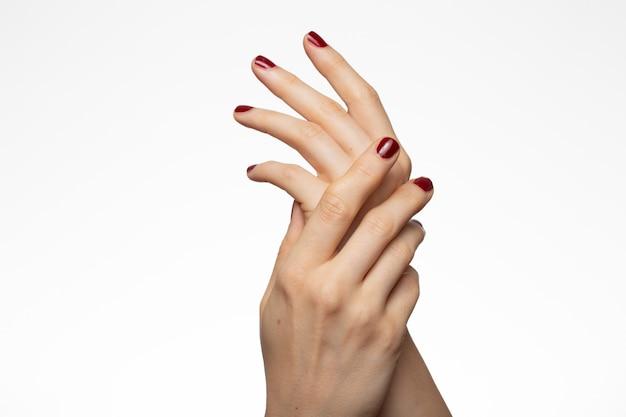 Hermosas manos femeninas con un esmalte de uñas rojo