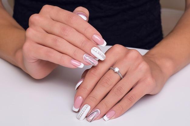 Hermosas manos femeninas con manicura francesa de lujo