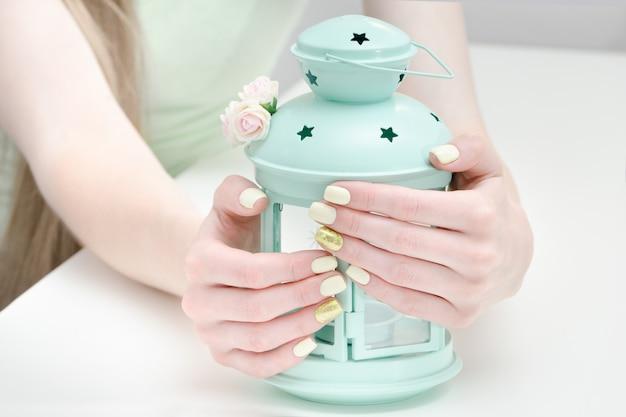 Hermosas manos femeninas con una manicura y una lámpara-candelabro sobre un fondo claro. amarillo con uñas doradas