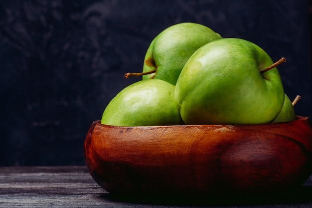 Hermosas manzanas en un tazón de madera